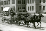 Covered wagon driving through town with passengers
