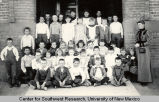 Group portrait of schoolchildren and teacher in front of the Third Ward School