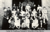 Group portrait of schoolchildren and teacher outside the Third Ward School