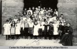 Group portrait of schoolchildren and teacher outside the Fourth Ward School