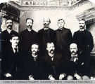 Group portrait of nine men -  man in back row at center identified as Taylor