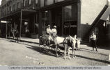 Two boys in a burro-drawn cart in front of the offices of the Daily Citizen newspaper