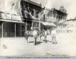 Two men standing with their horses in Gold Ave.