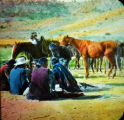 A group of Navajos with horses in background
