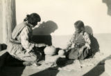 Maria Martinez showing a young potter how to polish a pot.