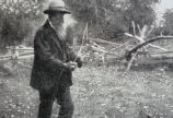 Unknown photograph of New England scenery with an old man in field with wood fence behind him