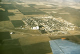 Aerial photograph of plane wing, and gridded town in gridded fields, Yoder KS