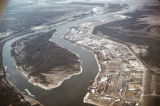 "Aerial photograph of urbanization along waterway, labeled as ""Industrial park on..."