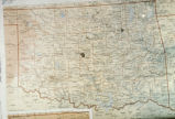 Photograph of unidentified map of Oklahoma highlighting Tulsa and Oklahoma City, using Lambert...