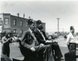 Belen NM parade L C Becker and Pat Gibson riding in an antique automobile or a Horseless carriage.