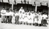 Father Lammert with a group of children in first communion attire