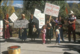 Dine  women and children holding protest signs at Big Mountain Defense March, Santa Fe, NM