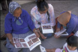 Weavers looking at Big Mountain Weaving Project brochures
