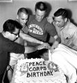 Peace Corps - anniversary - four men with cake