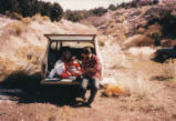 Harding Pegmatite field trip - man with child in back of truck
