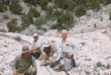 Harding Pegmatite mine - four men crouching on cart tracks