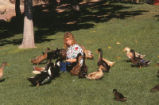 Duck Pond - woman seated surrounded by ducks