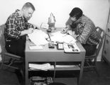 Student Publications - dormitories - two men at table