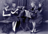 Four young violinists studio portrait
