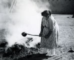 Santa Clara Pueblo potter removes her newly fired pot from the fire.