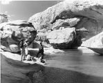 Indian guide showing visitors the natural water basin, Acoma Pueblo, New Mexico