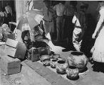 Indian pottery vendor under portal of Palace of the Governors during Fiesta, Santa Fe, New Mexico