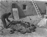 Julian Martinez tending pottery firing, San Ildefonso Pueblo, New Mexico
