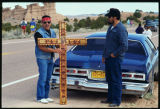 Man with cross and lowrider car, Good Friday pilgrimage to El Santuario de Chimayo, New Mexico