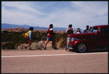 Family walking by lowrider, Good Friday pilgrimage to El Santuario de Chimayo, New Mexico