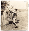 Woman hoeing in garden with two children, Nambe Pueblo, New Mexico