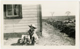 Calvin Traylor and puppy at railroad depot agent house, Loving, New Mexico