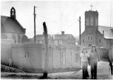 Two girls walking down street, church in background, San Juan Pueblo, New Mexico