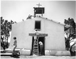 Workers repairing adobe church, New Mexico