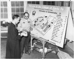 Brother George Hetzell and campus maintenance worker with College of Santa Fe campus map, Santa...