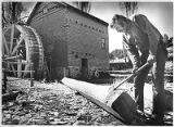 Man shaping a 10 foot oak beam for the old mill water wheel, El Rancho de las Golondrinas, La...