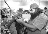 Leo Baldonado, left, shows a gun for sale to Van McDonald at Santa Fe flea market, New Mexico