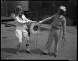 Champion rodeo cowgirl Grace Runyon in her show outfit, with unidentified man, Soldier Field,...