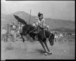 One of rodeo's famed cowgirls, Tad Lucas on bucking horse