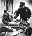 Detective Abbie Corriz left and officer Lenny Anaya examine three rifles and 700 rounds of...