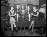 Unidentified cowgirls with rodeo trophies