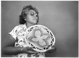 Basket maker Lydia Pesata from Dulce with Jicarilla Apache coil basket at Indian Market, Santa Fe,...
