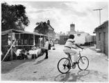 Man bicycles through the San Juan Pueblo arts and crafts festival
