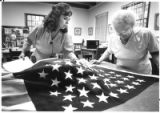 Diana De Santis, curator at Palace of the Governors, examines a 47-star American flag, a gift from...