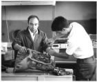Student and teacher work together during an auto mechanic class at the State School for Boys,...