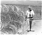 Larry T. Flood, Associate Warden at Penitentiary of New Mexico, walks the perimeter next to razor...