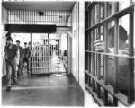 Inmates file by guard at the Penitentiary of New Mexico