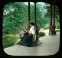 Couple on porch, woman in rocking chair