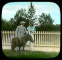 Man and woman leaning on white fence with miniature pony