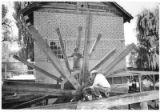 Hans Paap and Roger Swanson erect a waterwheel built by hand at El Rancho de las Golondrinas