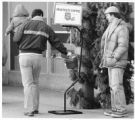 Man donates to Salvation Army bell ringer, Santa Fe, New Mexico